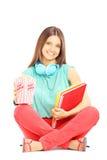 Uśmiechnięty studencki obsiadanie na podłoga i mienie notatnikach fotografia royalty free
