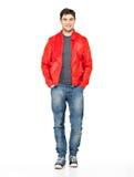 Uśmiechnięty szczęśliwy mężczyzna w czerwonej kurtce, niebieskich dżinsach i gymshoes. obraz stock