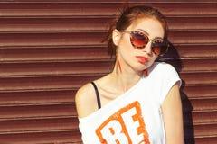 Uśmiechnięty szczęśliwy seksowny dziewczyny obsiadanie blisko ściany w okulary przeciwsłoneczni rudzielec z dużymi pełnymi wargam obraz stock