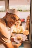 uśmiechnięty szef kuchni daje hamburgeru i francuza dłoniaki klienci od jedzenia obraz royalty free