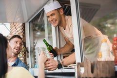 uśmiechnięty szef kuchni daje napojom klienci od zdjęcie stock