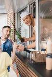 uśmiechnięty szef kuchni daje napojom klienci od jedzenia patrzeć i ciężarówki obrazy stock