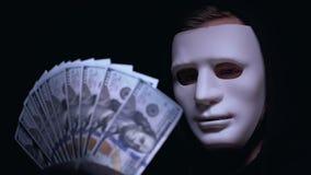 Uśmiechnięty szef mafia w maskowej trzyma wiązce dolary, rabunek, ciemny tło zbiory wideo