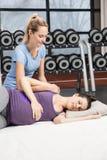 Uśmiechnięty trenera masowania kobieta w ciąży obraz stock