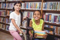 Uśmiechnięty uczeń w wózka inwalidzkiego mieniu rezerwuje w bibliotece Zdjęcia Stock