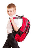 Uśmiechnięty uczeń z ciężkim plecakiem odizolowywającym na bielu Obrazy Stock
