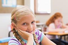 Uśmiechnięty ucznia obsiadanie przy jej biurkiem Fotografia Royalty Free