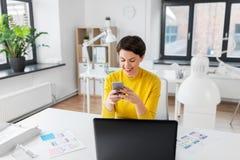 Uśmiechnięty ui projektant używa smartphone przy biurem obraz stock