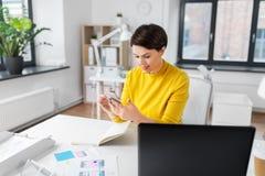 Uśmiechnięty ui projektant używa smartphone przy biurem zdjęcie stock