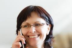 Uśmiechnięty w średnim wieku kobiety wezwanie telefonem obrazy stock