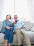 Uśmiechnięty w średnim wieku pary obsiadanie na leżance ogląda tv Obrazy Stock