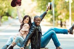 Uśmiechnięty wielokulturowy pary obsiadanie na longboard na ulicie i wydźwignięcie rękach obraz royalty free