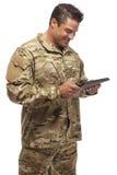 Uśmiechnięty wojsko żołnierz z pastylką w ręce Obrazy Stock