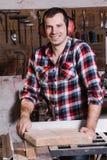 Uśmiechnięty woodworker Rozochocony młody męski cieśla opiera przy kółkowym stołem z drewnianą deską Zdjęcie Stock