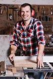 Uśmiechnięty woodworker Rozochocony młody męski cieśla opiera przy kółkowym stołem z drewnianą deską Obrazy Royalty Free