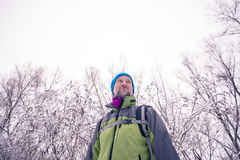 Uśmiechnięty wycieczkowicz jest relaksujący w zima lesie Zdjęcia Stock