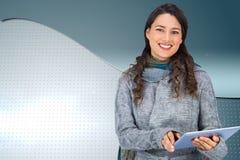 Uśmiechnięty wzorcowy jest ubranym zimy odzieżowy mienie jej pastylka Obrazy Royalty Free