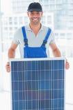 Uśmiechnięty złotej rączki mienia panel słoneczny w jaskrawym biurze Fotografia Stock