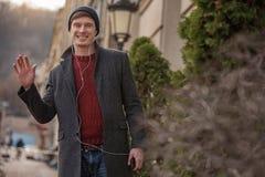 Uśmiechnięty zadowolony mężczyzna falowanie z ręką podczas gdy stojący zdjęcie stock