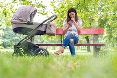 Uśmiechniętych potomstw macierzysty obsiadanie na ławce i używać jej telefon obrazy royalty free