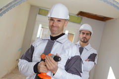 Uśmiechniętych profesjonalistów drużynowi budowniczowie ogląda salowego miejsce wokoło obraz royalty free