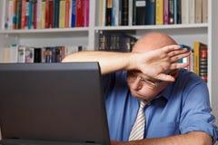 Uśmierzający stary człowiek z komputerem zdjęcia stock