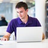 Używać jego laptop przystojny student collegu Obraz Stock