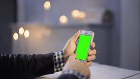 Używać Mądrze telefon na drewno stołu ręki gestów Vertical zakończenia zieleni wvarious ekranie up Obraz Stock