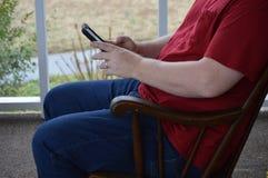 Używać mądrze telefon w kołysa krześle 3 zdjęcia stock