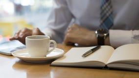Używać moment robić niektóre notatkom Ufny dorośleć mężczyzna writing coś w jego nutowym ochraniaczu podczas gdy siedzący przy st Zdjęcia Stock
