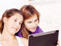 Używać pastylka komputer dwa nastoletniej dziewczyny obrazy stock