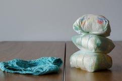 Używać pieluszki i czystych dzieci pantie na drewnianym stołowym backg zdjęcie royalty free