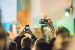 Używać posuwał się naprzód mobilnego nagranie, zabawa koncerty i pięknego oświetlenie, Szczery wizerunek tłum przy rockowym konce zdjęcie stock
