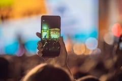 Używać posuwał się naprzód mobilnego nagranie, zabawa koncerty i pięknego oświetlenie, Szczery wizerunek tłum przy rockowym konce fotografia stock