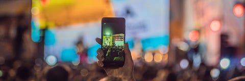 Używać posuwał się naprzód mobilnego nagranie, zabawa koncerty i pięknego oświetlenie, Szczery wizerunek tłum przy rockowym konce obraz stock