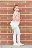 Używać słuchawki na ruchu Urocza mała dziewczynka jest ubranym bezprzewodową bluetooth słuchawki Modny mały dziecko z nastawczym obraz royalty free