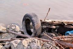 Używać samochodowa opona opuszczać w naturze Stara używać samochodu opona opuszczał rzucany kosztem woda Zdjęcie Stock