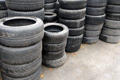 Używać samochodowe opony brogować w stosach przy junkyard Stary kół przetwarzać, spożytkowanie i Obrazy Stock