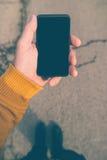Używać smartphone wiszącą ozdobę na ulicie Fotografia Stock