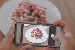 Używać telefon komórkowego, bierze fotografię deser Obraz Stock