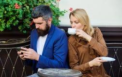 Używać telefon podczas gdy data filiżanki opatrunkowy dziewczyny togi ranek biel kobieta i mężczyzna z brodą relaksujemy w kawiar fotografia royalty free