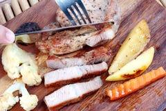 Używa nóż i rozwidla pokrojony wieprzowina stek fotografia stock