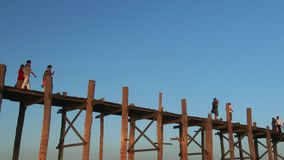U Bein Bridge in Amarapura, Mandalay, Laos. People crossing U Bein Bridge in Amarapura stock footage
