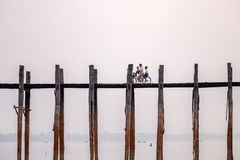 U Bein Bridge, Amarapura, Mandalay, Myanmar. Cycling on U Bein Bridge , Amarapura. The bridge crosses the Taungthaman lake and its length is 1.2 kilometres and Royalty Free Stock Image