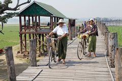 U Bein Bridge Amarapura, Myanmar. Burmese people are passing along the U Bein Bridge, Amarapura, Myanmar. U bein Bridge is a crossing that spans the Taugthaman Stock Image