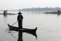 U-BEIN BRIDGE/AMARAPURA, MYANMAR AM 22. JANUAR 2016: Eine Frau navigiert ihr Boot auf dem Taungthaman See, der durch gekreuzt wir Stockbilder
