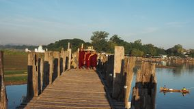 U-BEIN BRIDGE, AMARAPURA, MYANMAR SEPTEMBER 21: Buddhist monks on their daily walk across the bridge in the early morning hours. September 21, 2017,U Bein Stock Image