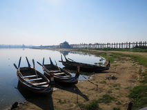 U Bein bridge and colorful wooden boats on bank of peaceful stil. U Bein bridge and colorful wooden rowing boats on bank of peaceful still water lake with birds Royalty Free Stock Photography