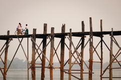 U Bein Bridge in Mandalay, Myanmar. Local people walking on U Bein Bridge at sunrise in Mandalay, Myanmar. U Bein Bridge is believed to be the oldest and longest Stock Photos
