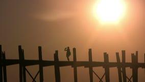 U Bein Bridge, Mandalay, Myanmar. U Bein Bridge at sunset: one tourist is photographying Ayeyarwady River, Mandalay, Myanmar stock video footage